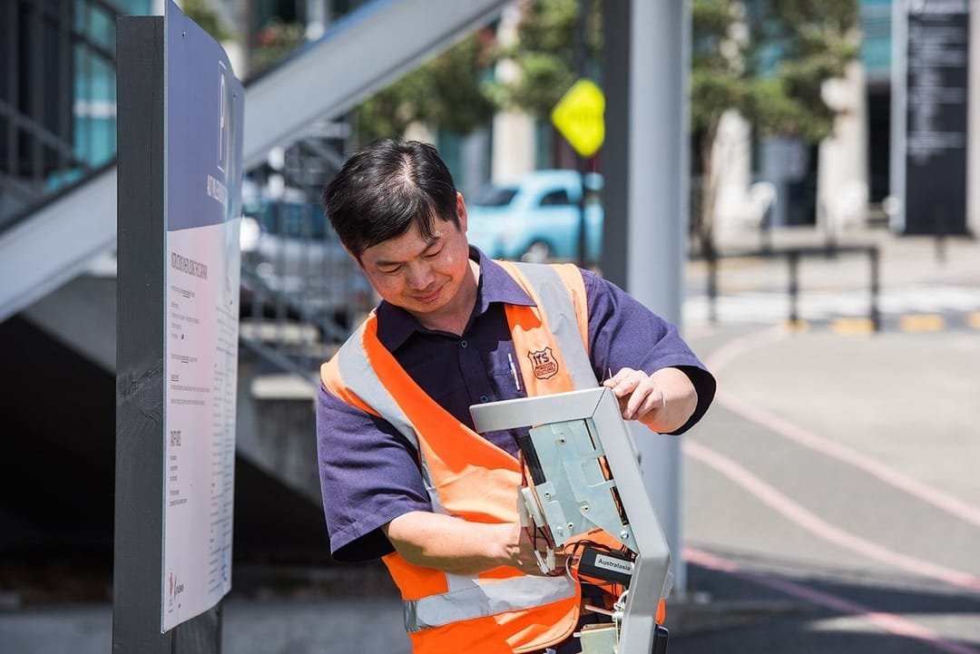 Armaguard employee working on parking ticket machine